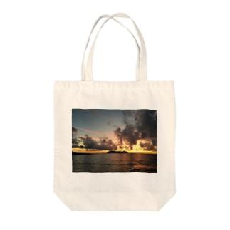 The sea where the setting sun shines  Tote bags